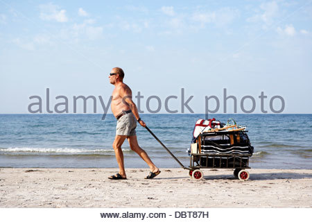 Senior man pulling cart with luggage on beach - Stock Photo