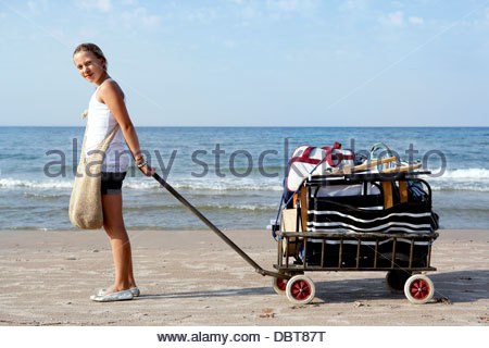 Girl (12-13) pulling cart with luggage on beach - Stock Photo
