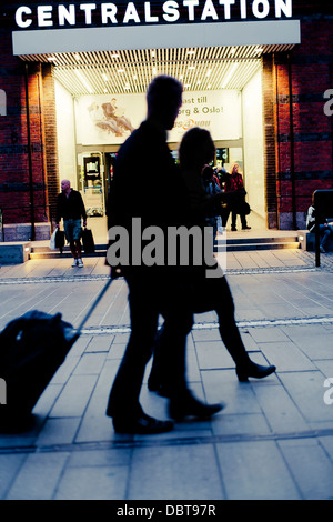 Silhouette of people in front of entrance to railroad station - Stock Photo