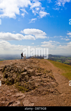 A lone walker rests by the trig point on the summit of Worcestershire Beacon - highest point of the Malvern Hills, - Stock Photo