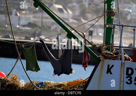 Fisherman's clothes hung out to dry in the sun on a fishing boat in the Kalk Bay Harbour near Cape Town. - Stock Photo