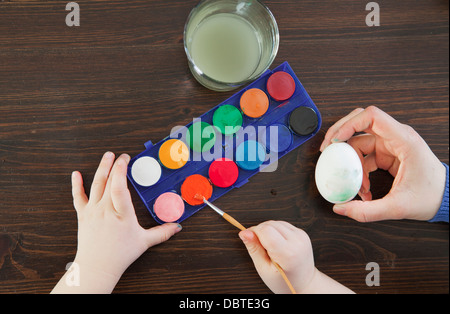 Elevated view of woman's and girl's hands (2-3) painting Easter egg - Stock Photo