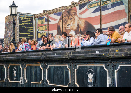 Sightseers on the Regents Canal bridge at Camden Lock, with a huge Union Jack and lion poster behind them, London, - Stock Photo