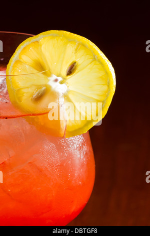 red cocktail isolated on a bar with a dark background garnished with a lemon slice on the rim of the glass - Stock Photo