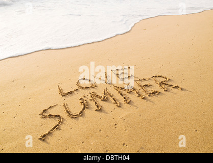 Text 'love summer' written in the sand on the beach with a wave. - Stock Photo