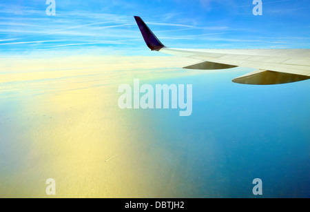 Wing of airplane flying over the ocean - Stock Photo