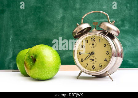 School time again. Clock and apples on teacher's table, green chalkboard in background. Back to school. - Stock Photo