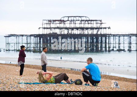 Woman having an early morning fitness workout with personal trainer on the beach near West Pier Brighton East Sussex - Stock Photo