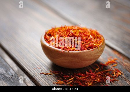 Saffron in wooden bowl on wooden background - Stock Photo