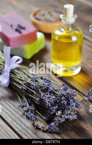 essential lavender oil, herbal soap and bunch of lavander flowers on wooden background. - Stock Photo