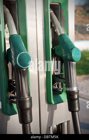 Closeup of fuel nozzles at a gas station. Gritty look. - Stock Photo