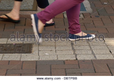 Close-up of peoples feet as they're walking along the pavement - Stock Photo