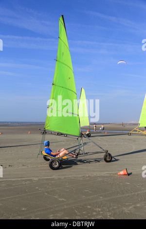 People driving sand yachting on the beach. They are learning and having fun. One man driving at the foreground - Stock Photo