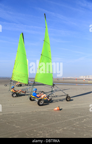 People driving sand yachting on the beach. They are learning and having fun. one man and one woman driving side - Stock Photo
