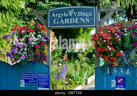 Entry sign and hanging flowers welcoming visitors to the beautiful Argyle village community gardens in West Vancouver, - Stock Photo