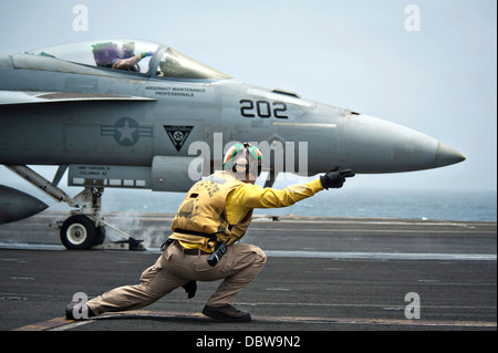 A US Navy Aviation Boatswain Mate signals a F/A-18E Super Hornet fighter aircraft to take off from the flight deck - Stock Photo