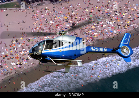 EC-120 COMMERCIAL HELICOPTER FLYING OVER CROWDED BEACH - Stock Photo