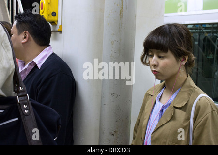 Young Japanese Woman waiting for Train on Subway Platform, Tokyo - Stock Photo