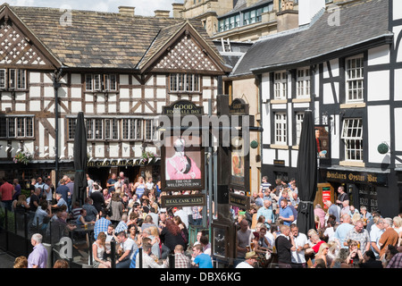 Crowds of people outside 16th century timbered The Old Wellington Inn 1552 in summer in Shambles Square Manchester - Stock Photo