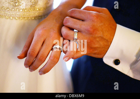 Newlywed bride and groom pinky promise after exchanging rings - Stock Photo