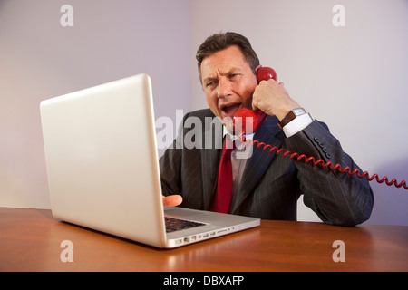 Angry man wearing a suit, shouting down a red telephone while sitting in front of a laptop on a desk. - Stock Photo