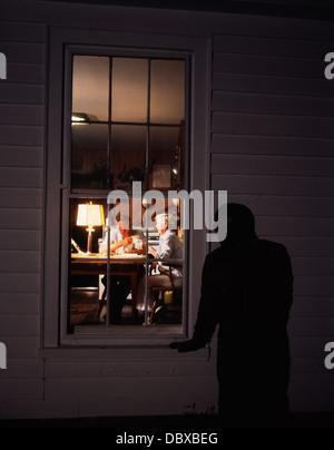 1980s CRIMINAL BLACK SKI MASK LURKING PEEK IN WINDOW AT ELDERLY COUPLE - Stock Photo