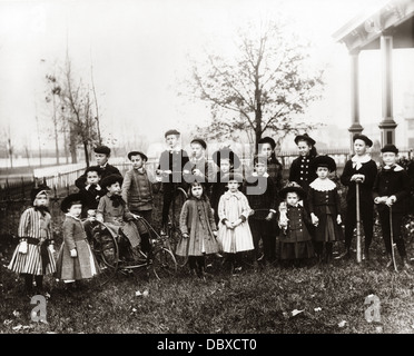 1890s 1900s POSED GROUP PORTRAIT OF 18 TURN OF THE 20TH CENTURY NEIGHBORHOOD CHILDREN ASSEMBLED IN SUBURBAN FRONT - Stock Photo