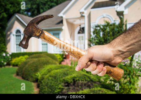 Man's hand holding hammer in front of a house indicating home improvement and maintenance. - Stock Photo