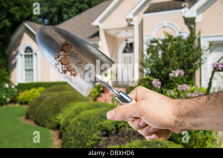 Man's hand holding dirty gardening spade in front of a home's front lawn. - Stock Photo