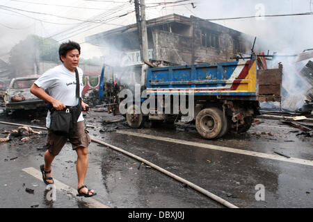 Cotabato, Philippines. 5th Aug, 2013. Bodies lay burnt in the street following a deadly car bomb explosion in the - Stock Photo