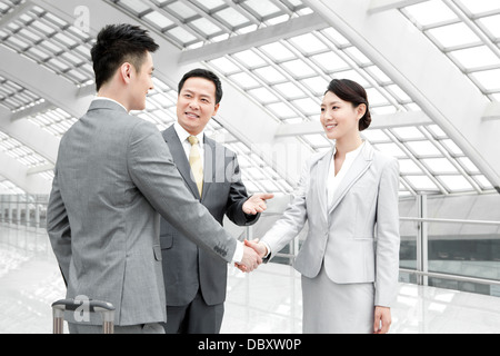 Business people shaking hands in airport lobby after being introduced - Stock Photo