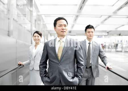 Confident business people on airport escalator - Stock Photo