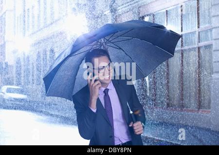 Happy businessman talking on cell phone under umbrella in rainy street - Stock Photo