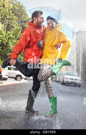 Happy couple in wellingtons splashing in rainy street - Stock Photo