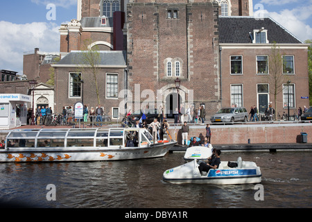 Pedal and passenger boats on Prinsengracht canal waterfront in front of Westerkerk in Amsterdam, Netherlands. - Stock Photo