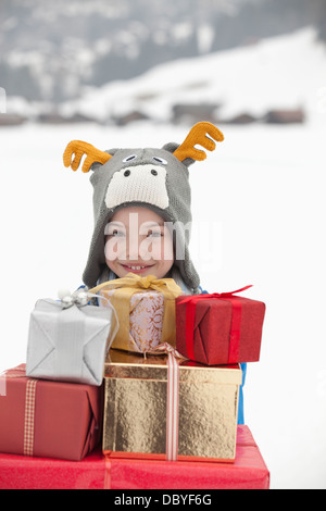 Portrait of smiling boy wearing reindeer hat and carrying stack of Christmas gifts in snow - Stock Photo