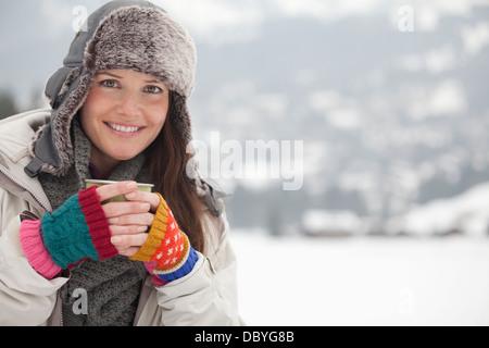 Portrait of happy woman in fur hat drinking coffee in snowy field - Stock Photo