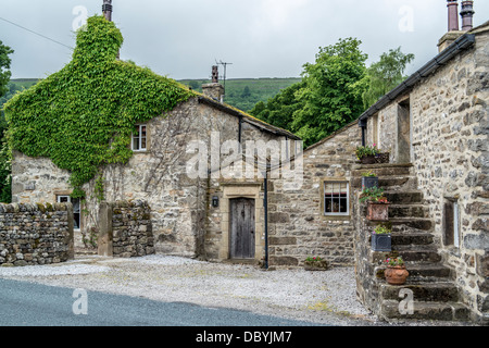 Small Cottages, steps leading up to doorway, flower pots on steps - Stock Photo