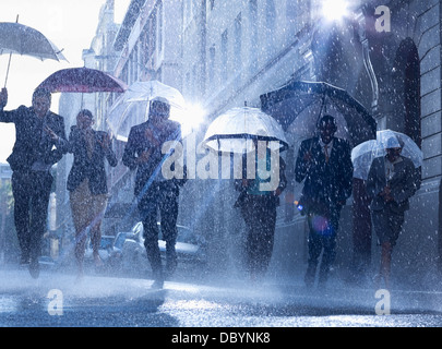 Business people with umbrellas running in rain - Stock Photo