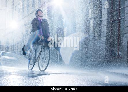 Businessman riding bicycle in rainy street - Stock Photo