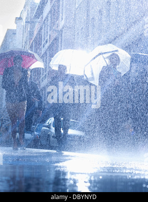 Business people with umbrellas in rain - Stock Photo