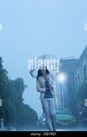 Happy woman with umbrella walking in rain