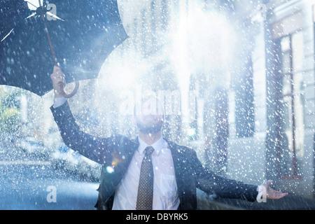 Enthusiastic man with broken umbrella in rain - Stock Photo