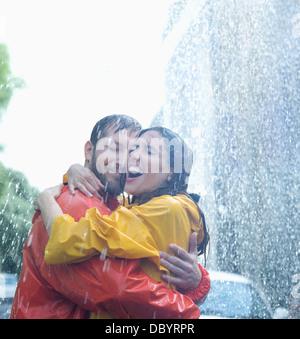 Happy couple hugging in rain - Stock Photo