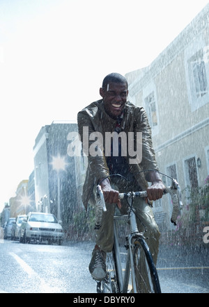 Happy businessman riding bicycle in rain - Stock Photo