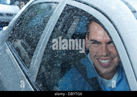 Portrait of smiling man in car - Stock Photo