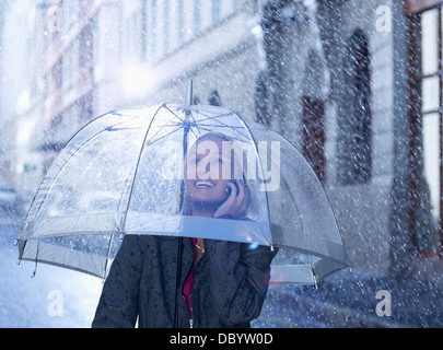 Smiling businesswoman talking on cell phone under umbrella in rainy street