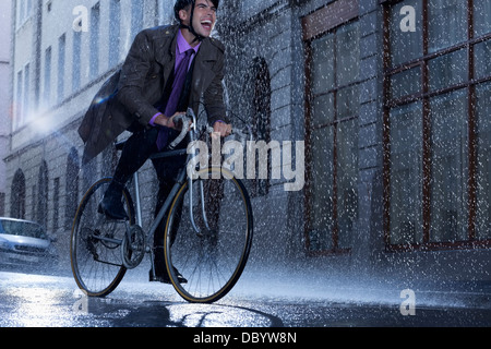 Enthusiastic businessman riding bicycle in rainy street - Stock Photo