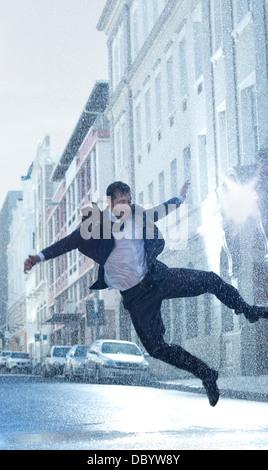 Businessman dancing in rainy street - Stock Photo