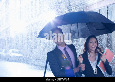 Happy businessman and businesswoman walking under umbrella in rain - Stock Photo